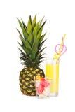 Ananas, ett exponeringsglas av ananasfruktsaft och stycken av fruktisolat Royaltyfri Foto