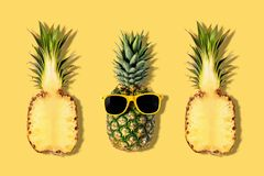 Ananas frais avec des lunettes de soleil sur le fond jaune Concept cr?atif de suumer photo libre de droits