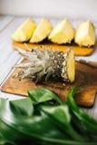 Ananas fresco affettato su un fondo di legno al sole Immagini Stock Libere da Diritti