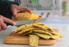 Ananas fresco di pulizia e di taglio Immagini Stock