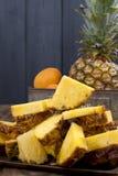 Ananas i brzoskwinie w metalu boksujemy na drewnianym tle abstrakcjonistycznego zdjęciu tła ramowej rocznik jednorodnego kosmos k fotografia royalty free