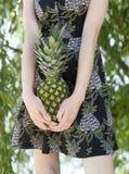 Ananas i händerna av den unga kvinnan Arkivfoto