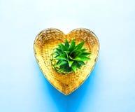 Ananas i vide- korg i formen av hjärta på blå bakgrund Begrepp för tropisk frukt arkivfoto
