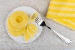 Ananas inscatolato in piattino, pezzo di ananas messo insieme sulla forcella Immagine Stock