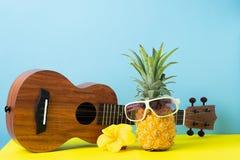 Ananas mûr jaune dans des lunettes de soleil Guitare sur le fond bleu jaune Museau dr?le d'un fruit tropical Concept de partie images stock