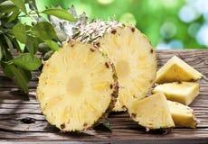 Ananas med skivor på en trätabell. Arkivbild