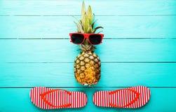 Ananas mit Gläsern und Pantoffeln auf blauem hölzernem Hintergrund Kopieren Sie Raum und Draufsicht Stockfotografie