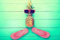 Ananas mit Gläsern und Pantoffeln auf blauem hölzernem Hintergrund Kopieren Sie Raum und Draufsicht Stockbilder
