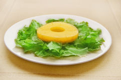 Ananas mit Grüns auf einer weißen Platte Stockfoto