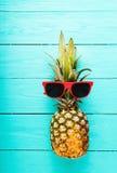 Ananas mit roter Sonnenbrille auf einem blauen Bretterboden Draufsicht und selektiver Fokus Stockfoto