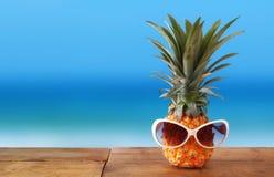 Ananas mit Sonnenbrille auf dem Tisch Strand und tropisches Thema Stockfotografie