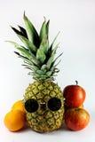 Ananas mit Sonnenbrillen und Frucht Stockfotografie