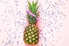 Ananas na różowym pastelowym modnym tle z confetti i gwiazdami Świąteczny tło dla pakunku fotografia royalty free