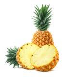 Ananas och halva stycken på vit bakgrund Arkivfoton