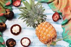 Ananas och Mangosteen på en blå bakgrund, bästa sikt royaltyfri fotografi