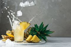 Ananas och is med färgstänk på trä Royaltyfria Foton
