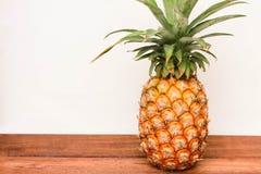 Ananas på trä och på vit bakgrund Royaltyfri Fotografi
