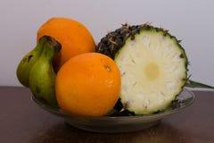 Ananas, pomarańcze i banany na talerzu na stole, Zdjęcie Royalty Free