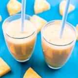 Ananas smoothie met verse ananas op houten blauwe lijst Stock Afbeeldingen