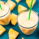 Ananas smoothie met verse ananas op houten blauwe lijst Royalty-vrije Stock Foto's