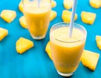 Ananas smoothie met verse ananas op houten blauwe lijst royalty-vrije stock foto