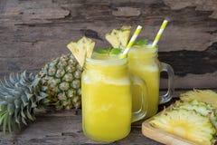 Ananas Smoothie- und Ananasfruchtgetränk morgens gesund an auf einem hölzernen Hintergrund stockfoto