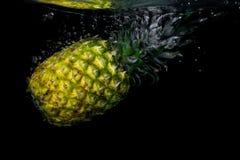 Ananas som faller i vatten på svart bakgrund arkivbilder