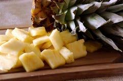 Ananas-Spitze und Stücke auf Schneidebrett Stockfoto