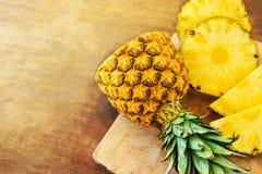 Ananas sul fondo di legno di struttura Intero ed ananas tropicale affettato sul tagliere di legno con lo spazio della copia Vista fotografia stock