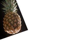 Ananas sullo strato nero isolato su bianco Immagini Stock
