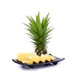 Ananas sur le plat noir d'isolement sur le fond blanc Image libre de droits
