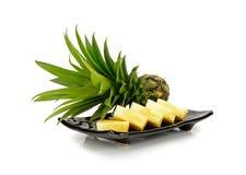 Ananas sur le plat noir d'isolement sur le fond blanc Photos libres de droits