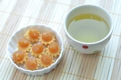 Ananas-Törtchen und eine Schale grüner Tee Stockbild
