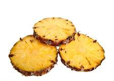 Ananas tre contro una priorità bassa bianca Immagini Stock