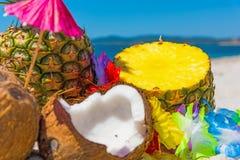 Ananas und hawaiische Halskette auf dem Strand Stockfotos