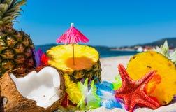 Ananas- und Kokosnusshälften auf dem Strand Stockfoto
