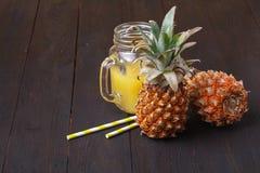 Ananas z tropikalnym owocowym sokiem, smoothie na ciemnym tle zdjęcia stock
