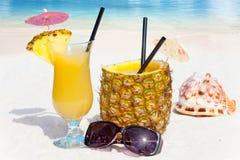 Ananasfrucht und -saft auf dem Strand Stockfoto