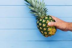 Ananasfruit op blauwe houten achtergrond ter beschikking wordt gehouden die royalty-vrije stock afbeelding