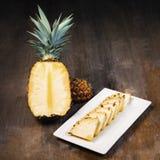 Ananasfrukt klippte halva, fjärdedelen och kilar och visat på den vita plattan och träbakgrund Fyrkantig sammansättning Saftig or arkivbilder