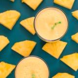 Ananasfruktsaft i ett exponeringsglas och en ananas bär frukt omkring Arkivbilder