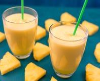 Ananasfruktsaft i ett exponeringsglas och en ananas bär frukt omkring Arkivbild