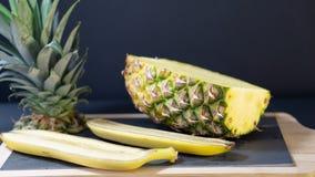 Ananasowa połówka na obramiającej kamień desce ciie w połówce, wokoło dwa banan połówki fotografia royalty free