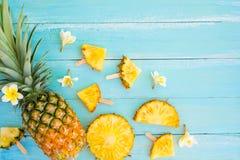 Ananasowi plasterki na drewnianej deski błękitnym kolorze Zdjęcia Stock