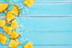 Ananasowi popsicle kije z lodem na drewnianej deski błękitnym kolorze Zdjęcia Royalty Free