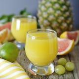 Ananasowy koktajl lub sok w szkle z słoma i owoc na tle ananas, pomarańcze, grapefruitowy -, wapno i winogrona greaser fotografia stock