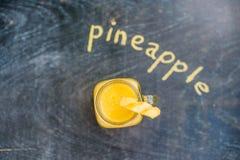 Ananasowy koktajl z plasterkiem na drewniany tło i inskrypcja w kredzie Tropikalny pojęcie Obrazy Royalty Free