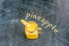 Ananasowy koktajl z plasterkiem na drewniany tło i inskrypcja w kredzie Tropikalny pojęcie Zdjęcie Royalty Free