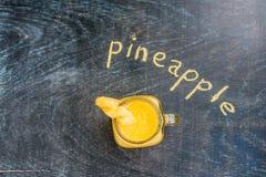 Ananasowy koktajl z plasterkiem na drewniany tło i inskrypcja w kredzie Tropikalny pojęcie Zdjęcia Stock