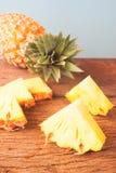 Ananasowy plasterek na nieociosanym drewnianym stole Fotografia Royalty Free